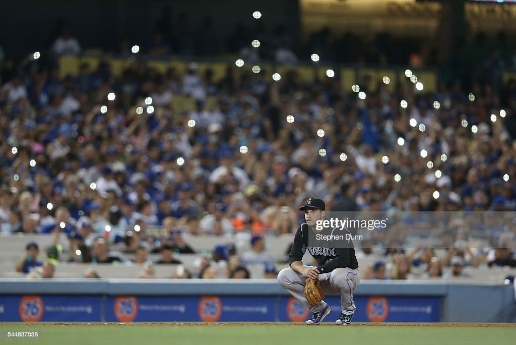 Third baseman Nolan Arenado #28 of the Colorado Rockies squats in the field as fans light their cell phones during the seventh inning in the game with the Los Angeles Dodgers at Dodger Stadium on July 2, 2016 in Los Angeles, California.