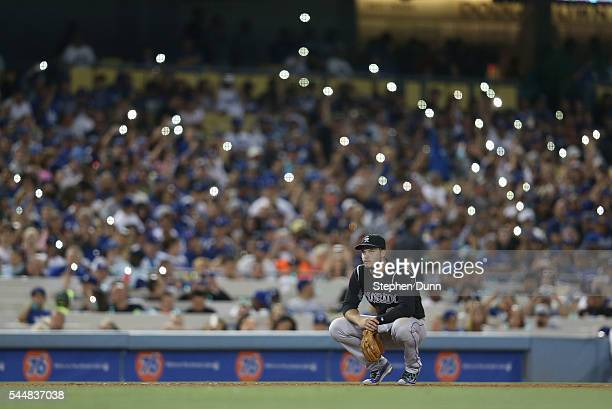 Third baseman Nolan Arenado of the Colorado Rockies squats in the field as fans light their cell phones during the seventh inning in the game with...