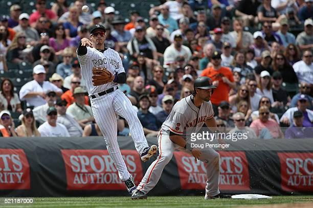 Third baseman Nolan Arenado of the Colorado Rockies throws on Hunter Pence of the San Francisco Giants as he holds Angel Pagan of the San Francisco...