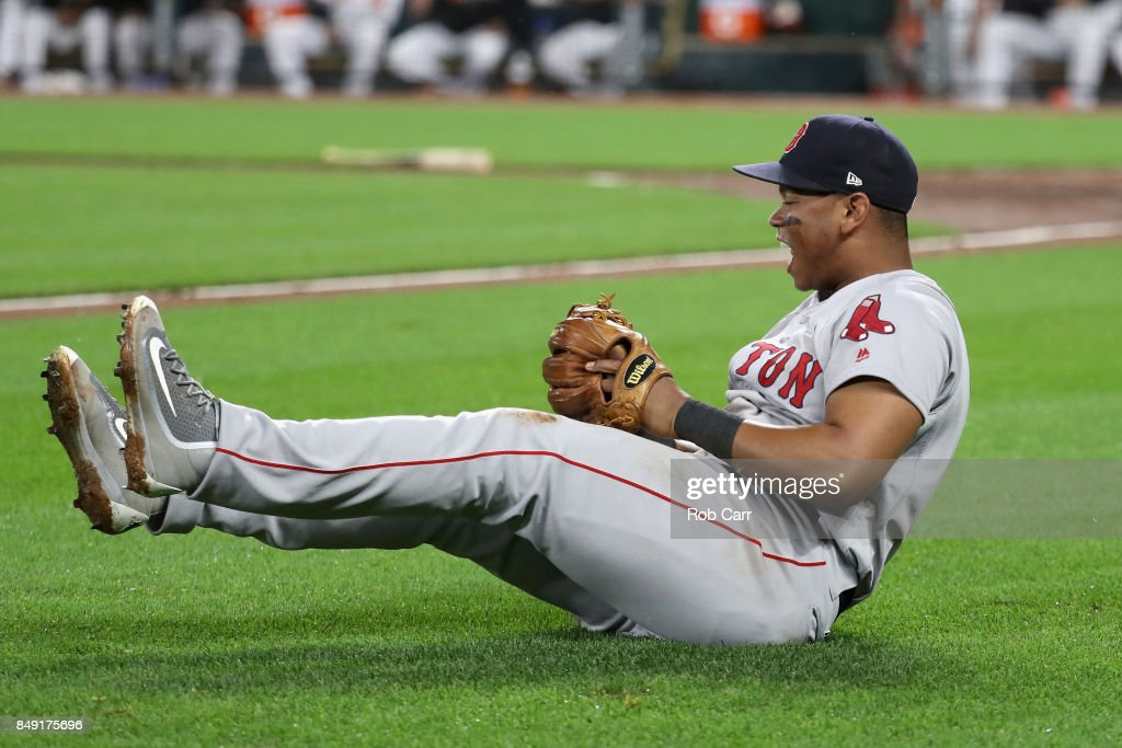 Third baseman Rafael Devers #11 of the Boston Red Sox falls to the ground after catching the cut off throw against the Baltimore Orioles in the second inning at Oriole Park at Camden Yards on September 18, 2017 in Baltimore, Maryland.