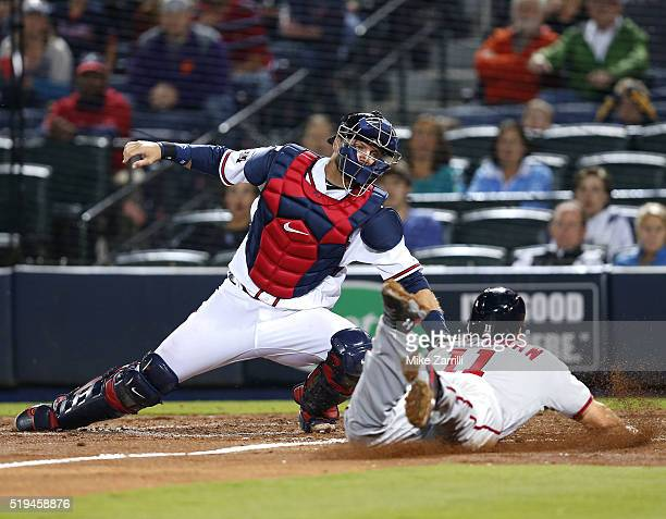 Third baseman Ryan Zimmerman of the Washington Nationals slides in safely past catcher AJ Pierzynski of the Atlanta Braves to score the tying run in...