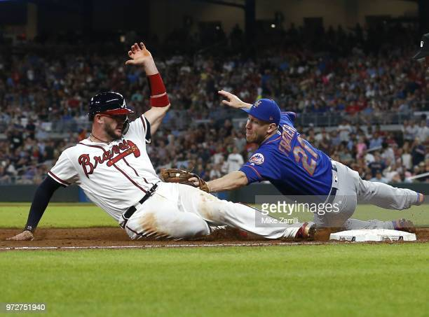 Third baseman Todd Frazier of the New York Mets tags out catcher Tyler Flowers of the Atlanta Braves at third base in the sixth inning during the...