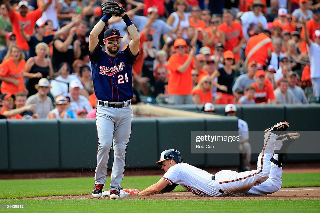 Third baseman Trevor Plouffe #24 of the Minnesota Twins holds the ball as Ryan Flaherty #3 of the Baltimore Orioles slides into third for a triple in the sixth inning at Oriole Park at Camden Yards on August 31, 2014 in Baltimore, Maryland.