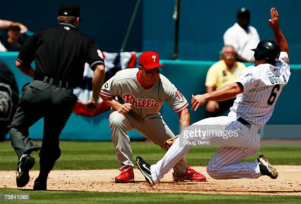 Third baseman Wes Helms of the Philadelphia Phillies tags out Dan Uggla of the Florida Marlins to complete a double play as umpire Adam Dowdy gets in...