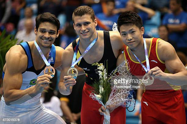 Third Francisco Carlos Barreto Junior of Brazil first Lukas Dauser of Germany and second Xiaodong Zhu of China celebrates on the podium after...