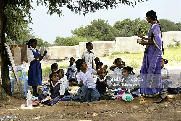 Third grade students in a rural Telegu language class held under a tamarind tree try to answer a question as a teacher corrects their answers...