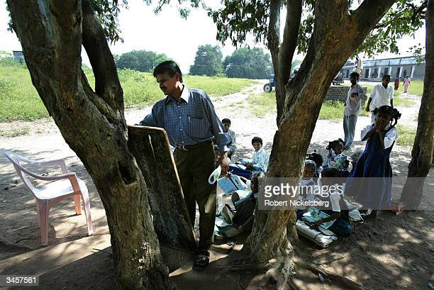 Third grade students watch as their teacher writes on a movable blackboard in a rural school's social studies class held under a Tamarind tree...
