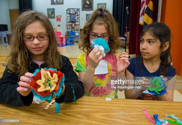 Third grader Kaitlyn Wannall left her second grade sister Eliana center and second grader Karen Depaz participate in constructing flowers from tissue...