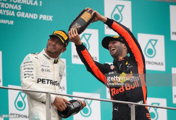 Third place finisher Daniel Ricciardo of Australia and Red Bull Racing celebrates with second place finisher Lewis Hamilton of Great Britain and...