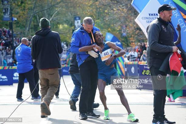 TOPSHOT Third place finisher Girma Bekele Gebre of Ethiopia is helped during the Professional Men's Finish during the 2019 TCS New York City Marathon...