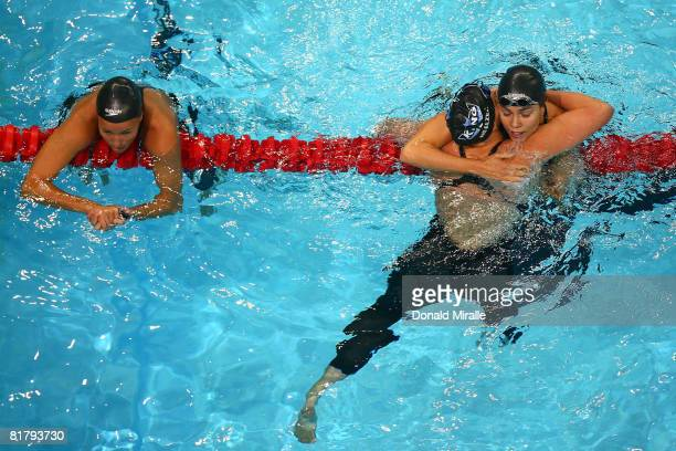 Third place finisher Hayley McGregory hangs on the lane line as second place finisher Margaret Hoelzer hug winner Natalie Coughlin after the final of...