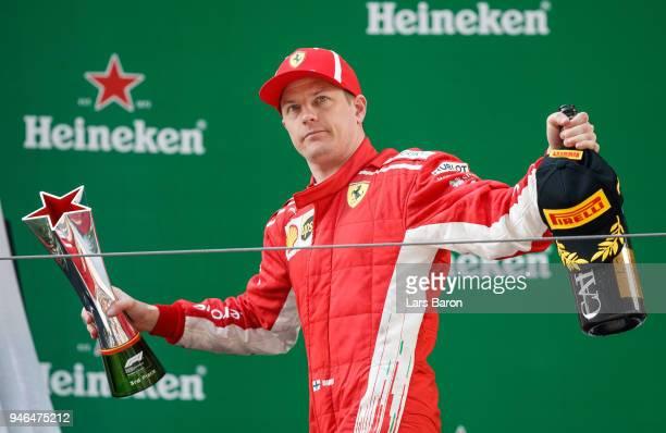 Third place finisher Kimi Raikkonen of Finland and Ferrari celebrates on the podium during the Formula One Grand Prix of China at Shanghai...