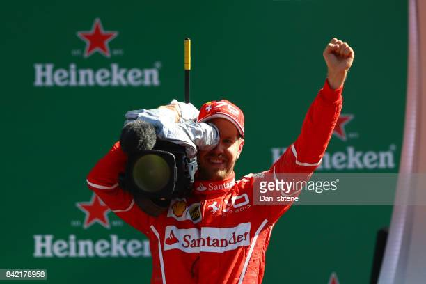 Third place finisher Sebastian Vettel of Germany and Ferrari films the crowd from the podium during the Formula One Grand Prix of Italy at Autodromo...