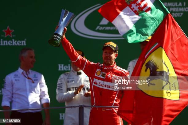 Third place finisher Sebastian Vettel of Germany and Ferrari celebrates on the podium during the Formula One Grand Prix of Italy at Autodromo di...