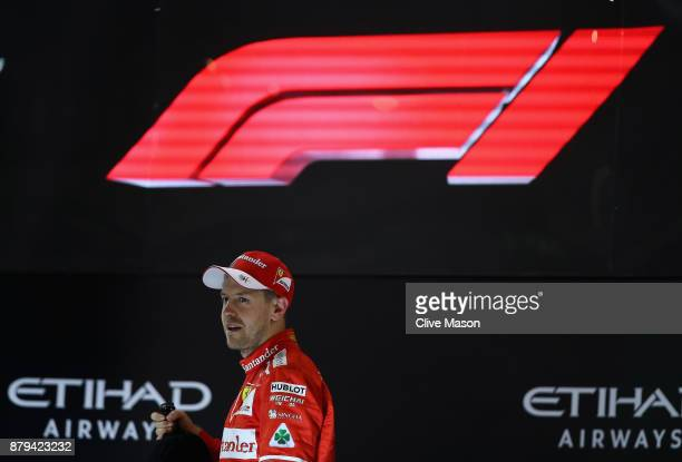 Third place finisher Sebastian Vettel of Germany and Ferrari on the podium during the Abu Dhabi Formula One Grand Prix at Yas Marina Circuit on...