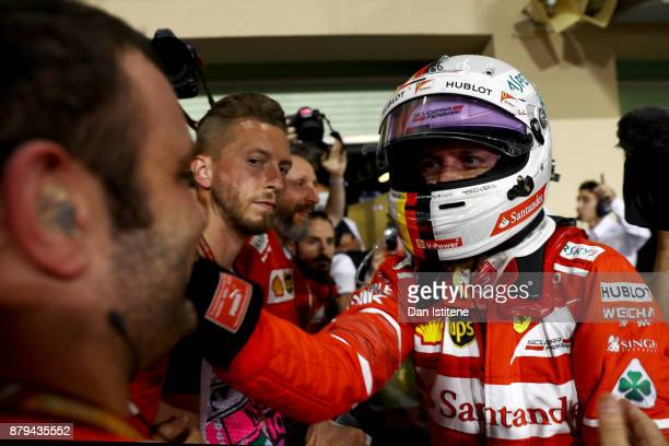 Third place finisher Sebastian Vettel of Germany and Ferrari celebrates with his team in parc ferme during the Abu Dhabi Formula One Grand Prix at...
