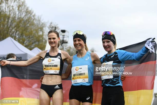 Third place Germany's Rabea Schoeneborn, Forth placed Germany's Laura Hottenrott and winner Germany's Katharina Steinrueck pose with the German flag...