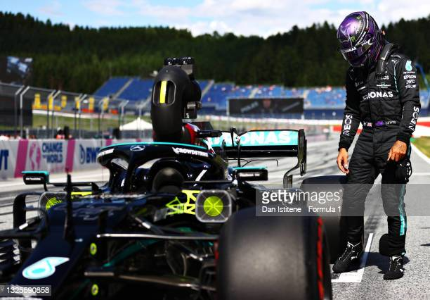 Third place qualifier Lewis Hamilton of Great Britain and Mercedes GP inspects his car in parc ferme during qualifying ahead of the F1 Grand Prix of...
