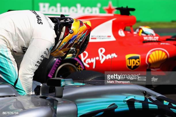 Third place qualifier Lewis Hamilton of Great Britain and Mercedes GP pulls into parc ferme behind pole position qualifier Sebastian Vettel of...