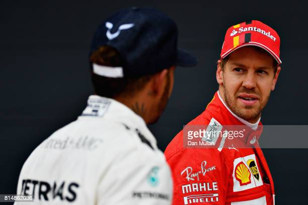 Third place qualifier Sebastian Vettel of Germany and Ferrari talks with pole position qualifier Lewis Hamilton of Great Britain and Mercedes GP in...
