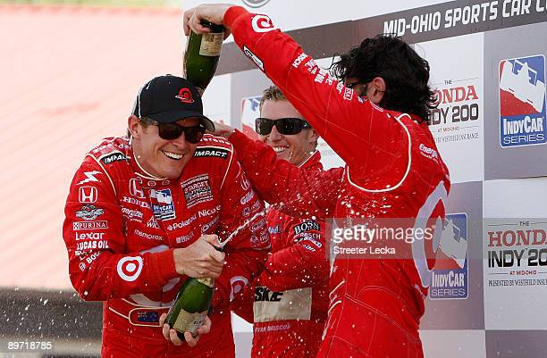 Third place Ryan Briscoe driver of the Dallara Honda watches as Second place Dario Franchitti pours champagne on teammate and champion Scott Dixon...