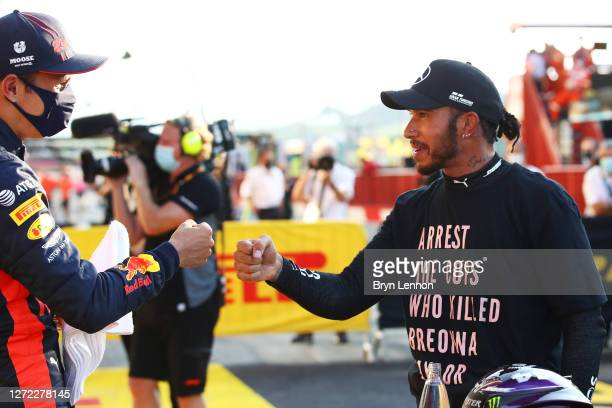 Third placed Alexander Albon of Thailand and Red Bull Racing speaks with race winner Lewis Hamilton of Great Britain and Mercedes GP in parc ferme...