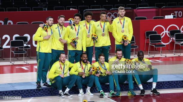 Third placed Australia's players pose for pictures on the podium with their bronze medals during the medal ceremony for the men's basketball...