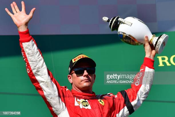 Third placed Ferrari's Finnish driver Kimi Raikkonen celebrates with his trophy after the Formula One Hungarian Grand Prix at the Hungaroring circuit...
