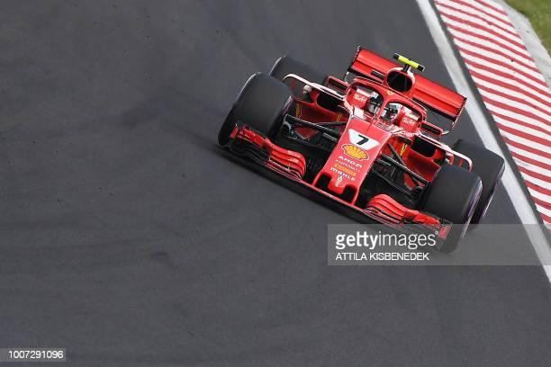 TOPSHOT Third placed Ferrari's German Driver Kimi Raikkonen steers his car during the Formula One Hungarian Grand Prix at the Hungaroring circuit in...