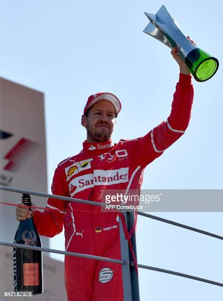 Third placed Ferrari's German driver Sebastian Vettel celebrates on the podium after the Italian Formula One Grand Prix at the Autodromo Nazionale...