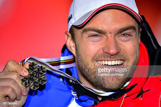 Third placed France's David Poisson poses with silver medal after the men's downhill event of the 2013 Ski World Championships in Schladming Austria...