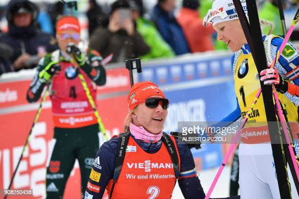 Third placed Kaisa Makarainen of Finland congratulates second placed Anastasiya Kuzmina of Slovakia after crossing the finish line of the Women's 125...