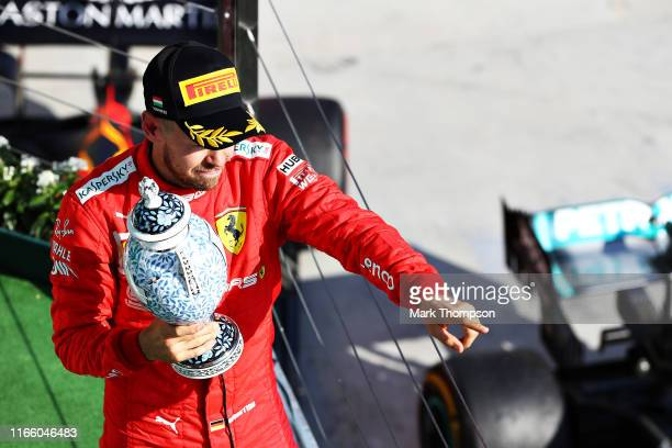 Third placed Sebastian Vettel of Germany and Ferrari celebrates on the podium during the F1 Grand Prix of Hungary at Hungaroring on August 04 2019 in...