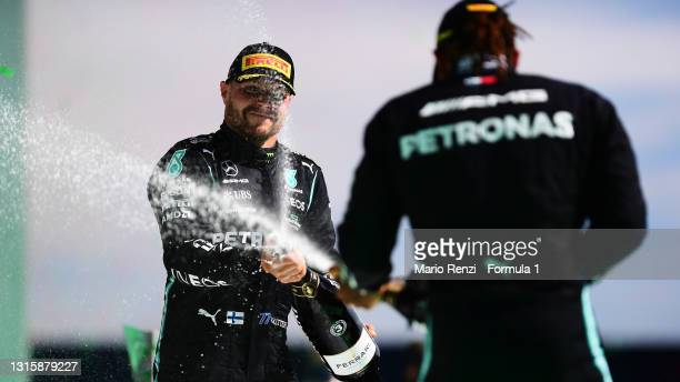 Third placed Valtteri Bottas of Finland and Mercedes GP and race winner Lewis Hamilton of Great Britain and Mercedes GP celebrate with sparkling wine...