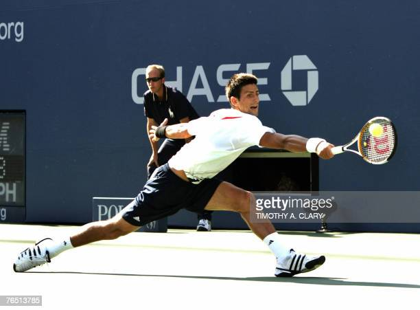 Third seed Novak Djokovic of Serbia hits a return to twenty-third-seeded Argentinian Juan Monaco during their fourth round match at the US Open...