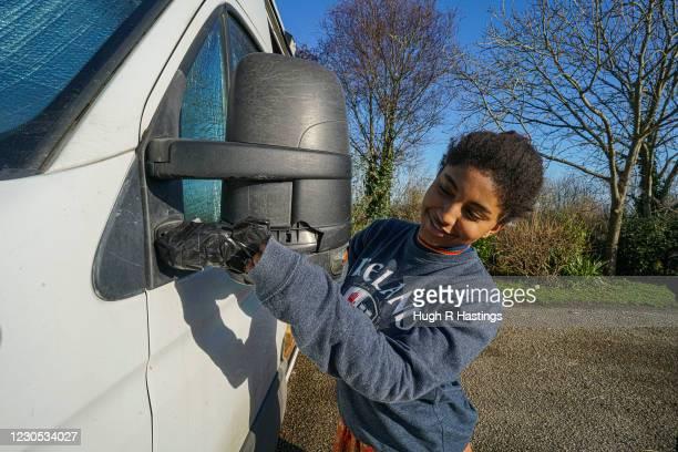 Third year student at Falmouth University, Yasmine Fosu, repairs a broken mirror on her van on January 07, 2021 in Falmouth, England. YasmineÕs...