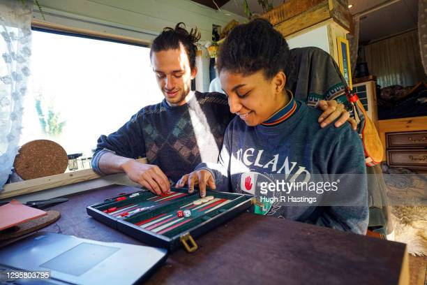 Third year students at Falmouth University, Max Richmond and Yasmine Fosu play backgammon in their van on January 07, 2021 in Falmouth, England. Max,...
