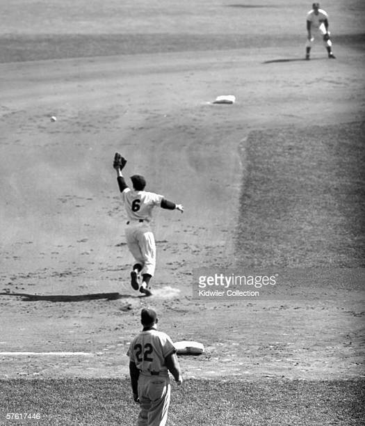 Thirdbaseman Andy Carey of the New York Yankees deflects the line drive off the bat of Jackie Robinson of the Brooklyn Dodgers in the second inning...