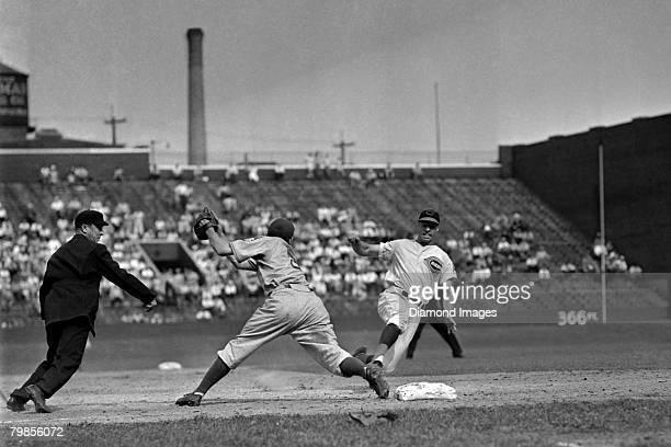 Thirdbaseman Bill Werber of the Cincinnati Reds steals thirdbase as thirdbaseman Pete Coscarat of the Brooklyn Dodgers receives the throw too late...