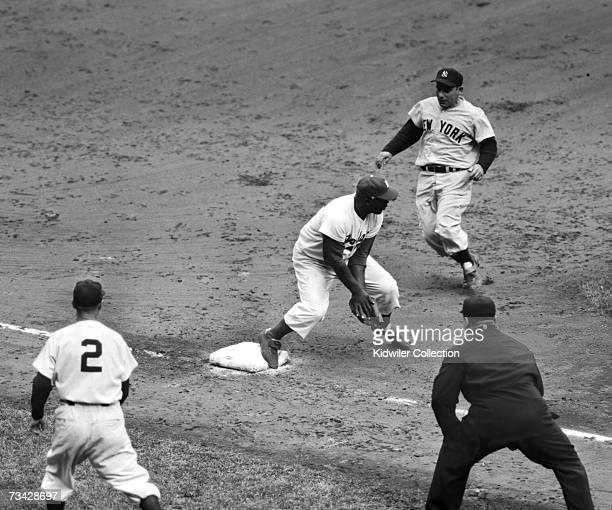 Thirdbaseman Jackie Robinson of the Brooklyn Dodgers holds onto the ball to retire Yogi Berra of the New York Yankees during the fourth game of the...