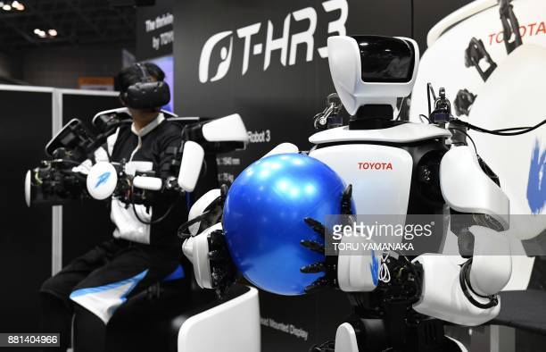Thirdgeneration humanoid robot THR3 developed by Japan's auto maker Toyota holds a rubber ball as it mirrors its operator's movements at the...