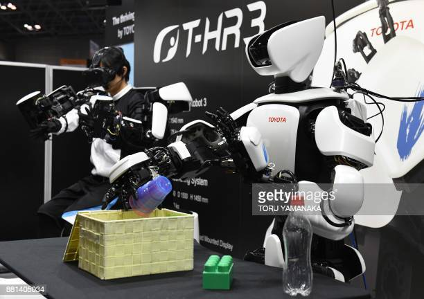 Thirdgeneration humanoid robot THR3 developed by Japan's auto maker Toyota puts plastic cups into a box as it mirrors its operator's movements at the...