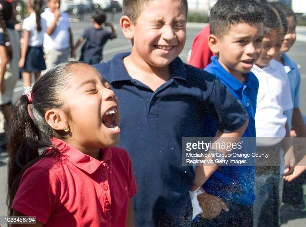 Thirdgrade Garfield Elementary students Rocio Villegas from left Sergio FragozoMarroquin and Bryan Martinez get treated to a cool spray of water...