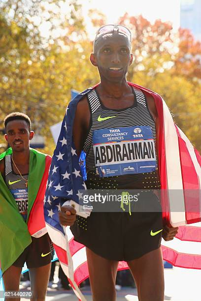 Thirdplace finisher Abdi Abdirahman of the United States celebrates with the American flag alongside firstplace finisher Ghirmay Ghebreslassie of...