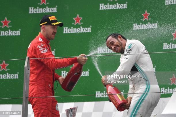 Thirdplaced Ferrari's German driver Sebastian Vettel sprays champagne at winner Mercedes' British driver Lewis Hamilton on the podium as they...