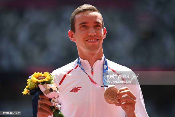 Third-placed Poland's Patryk Dobek celebrates on the podium with his bronze medal after competing in the men's 800m event during the Tokyo 2020...