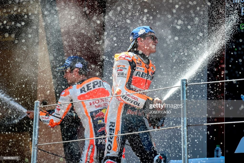 TOPSHOT - Third-placed Repsol Honda Team's Spanish rider Dani Pedrosa and second-placed Repsol Honda Team's Spanish rider Marc Marquez spary cava on the podium after the Moto GP race of the Catalunya Grand Prix at the Montmelo racetrack near Barcelona on June 11, 2017. / AFP PHOTO / Josep LAGO