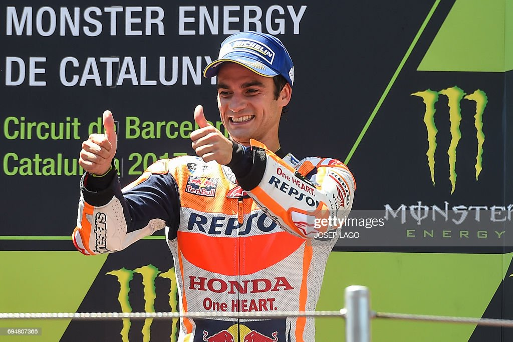 Third-placed Repsol Honda Team's Spanish rider Dani Pedrosa gives the thumbs-up on the podium with the trophy after the Moto GP race of the Catalunya Grand Prix at the Montmelo racetrack near Barcelona on June 11, 2017. / AFP PHOTO / Josep LAGO