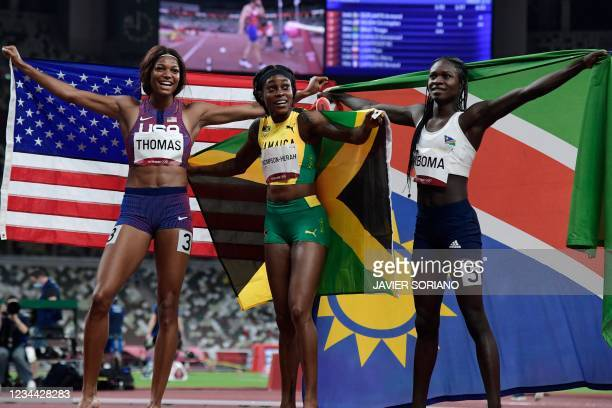 Third-placed USA's Gabrielle Thomas, race winner Jamaica's Elaine Thompson-Herah and second-placed Namibia's Christine Mboma celebrate with their...