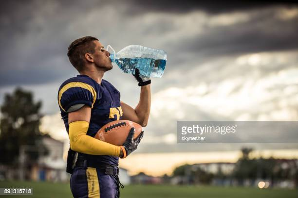 Thirsty American football player drinking fresh water on playing field.